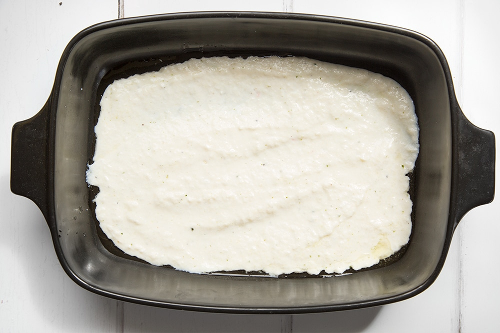 The cheese sauce is poured into a dish ready to bake