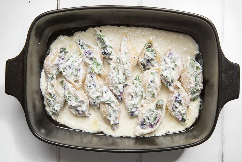 The ricotta blackberry stuffed giant pasta shells are added to the dish