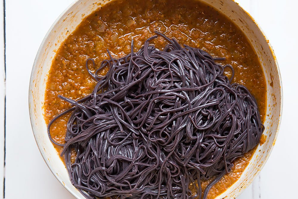 The cooked, drained noodles are added to the tomato pasta sauce