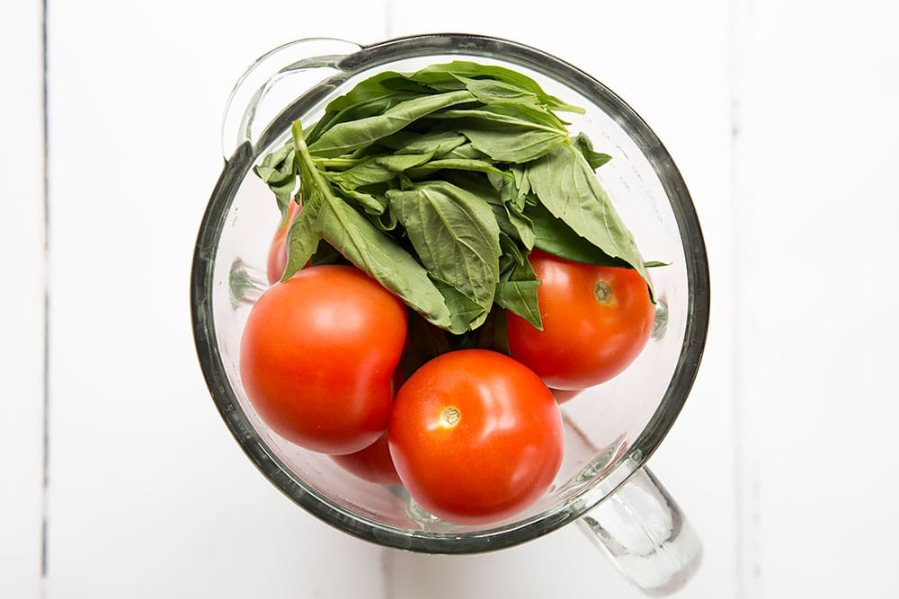 Tomatoes and basil, shown in a food blender