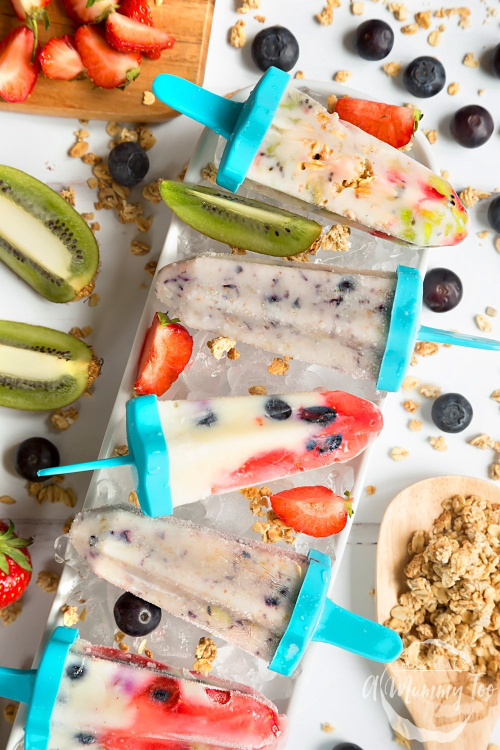 Frozen fruit and yogurt lollies shown surrounded by kiwis, strawberries, blueberries and granola. Perfect for a refreshing treat this Summer!