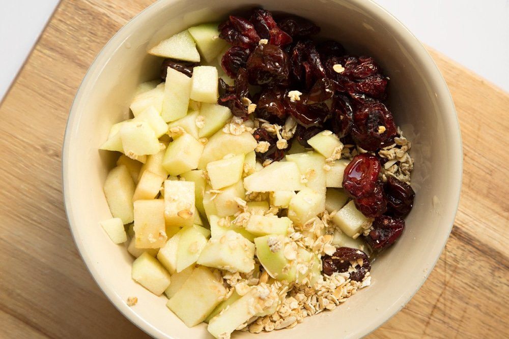 Granola, apples, cherries and honey in a bowl