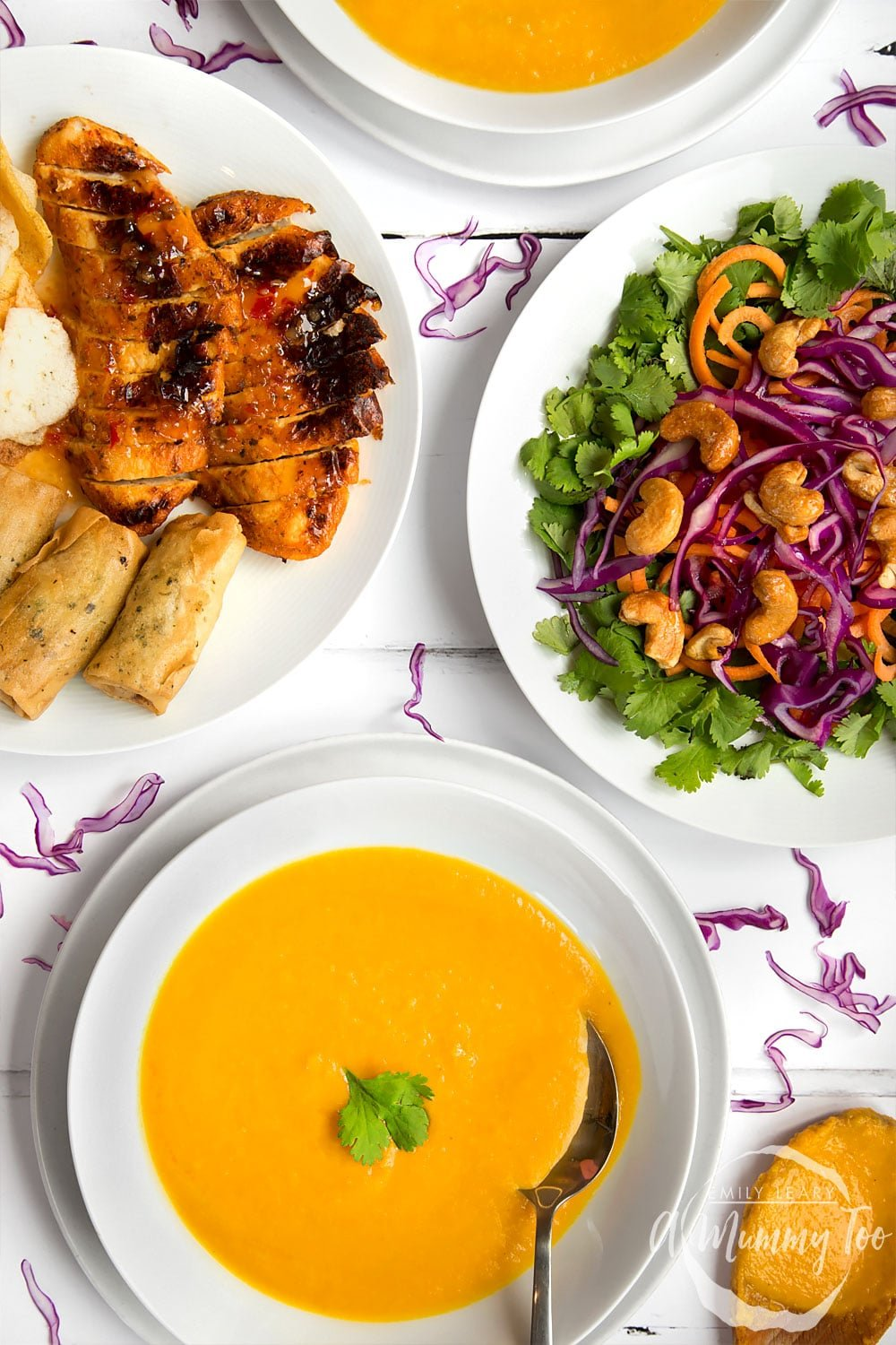 Thai curry and coconut soup, shown on a table with other Thai inspired dishes