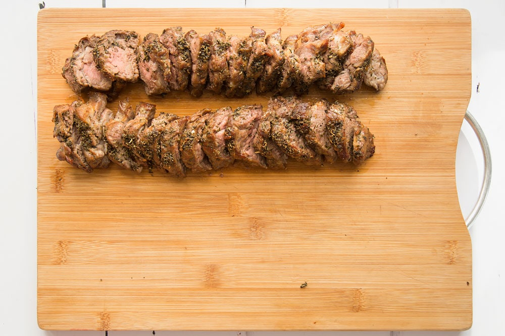 Freshly cooked Welsh lamb, shown on a chopping board ready to assemble into a herb crusted Welsh Lamb in a quick coriander flatbread wrap