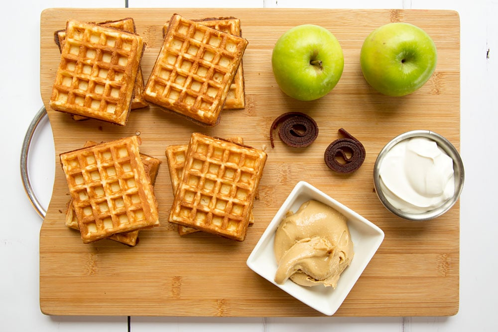 Ingredients to make the waffle apple burgers, shown on a chopping board