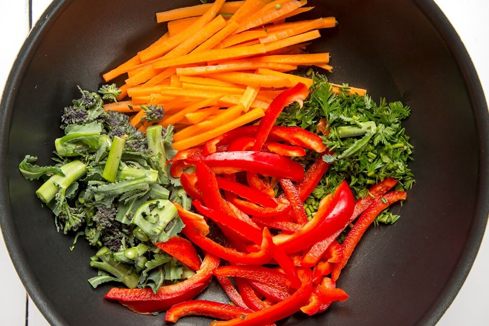Preparing the stir fry in a pan, starting with chopped vegetables