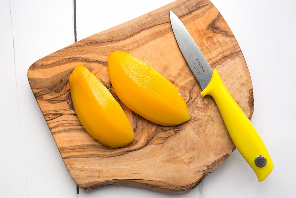 Preparing the mango by slicing into cubes