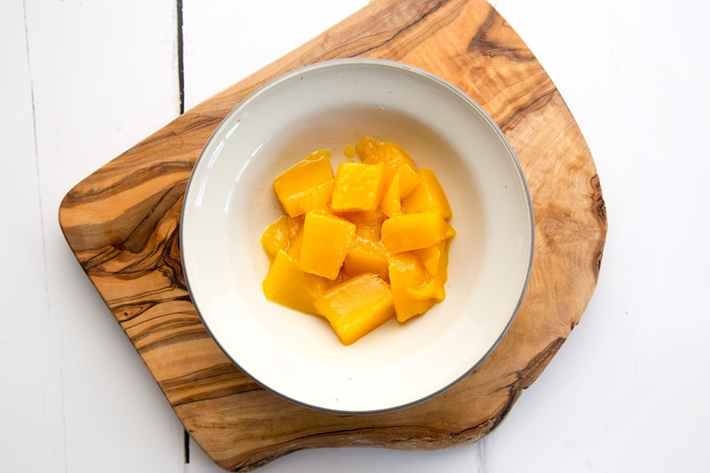 The mango cubes are placed in bowls, forming the bottom layer