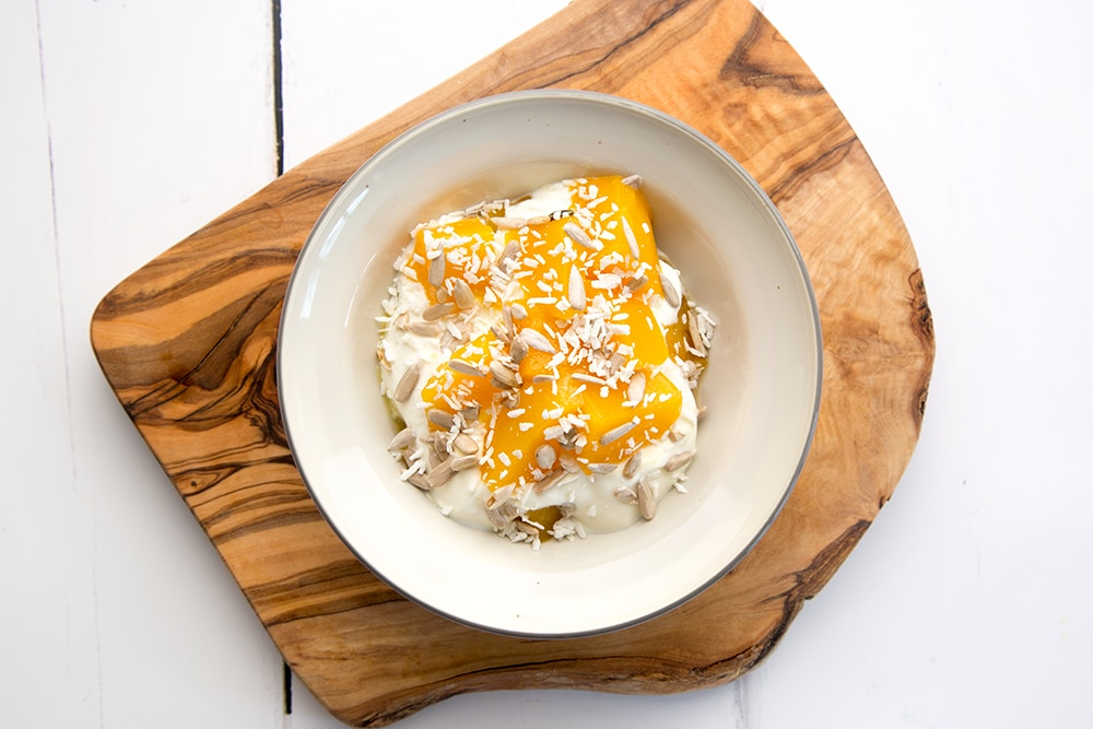 Sprinkle desiccated coconut on top to finish the yogurt and mango breakfast bowls