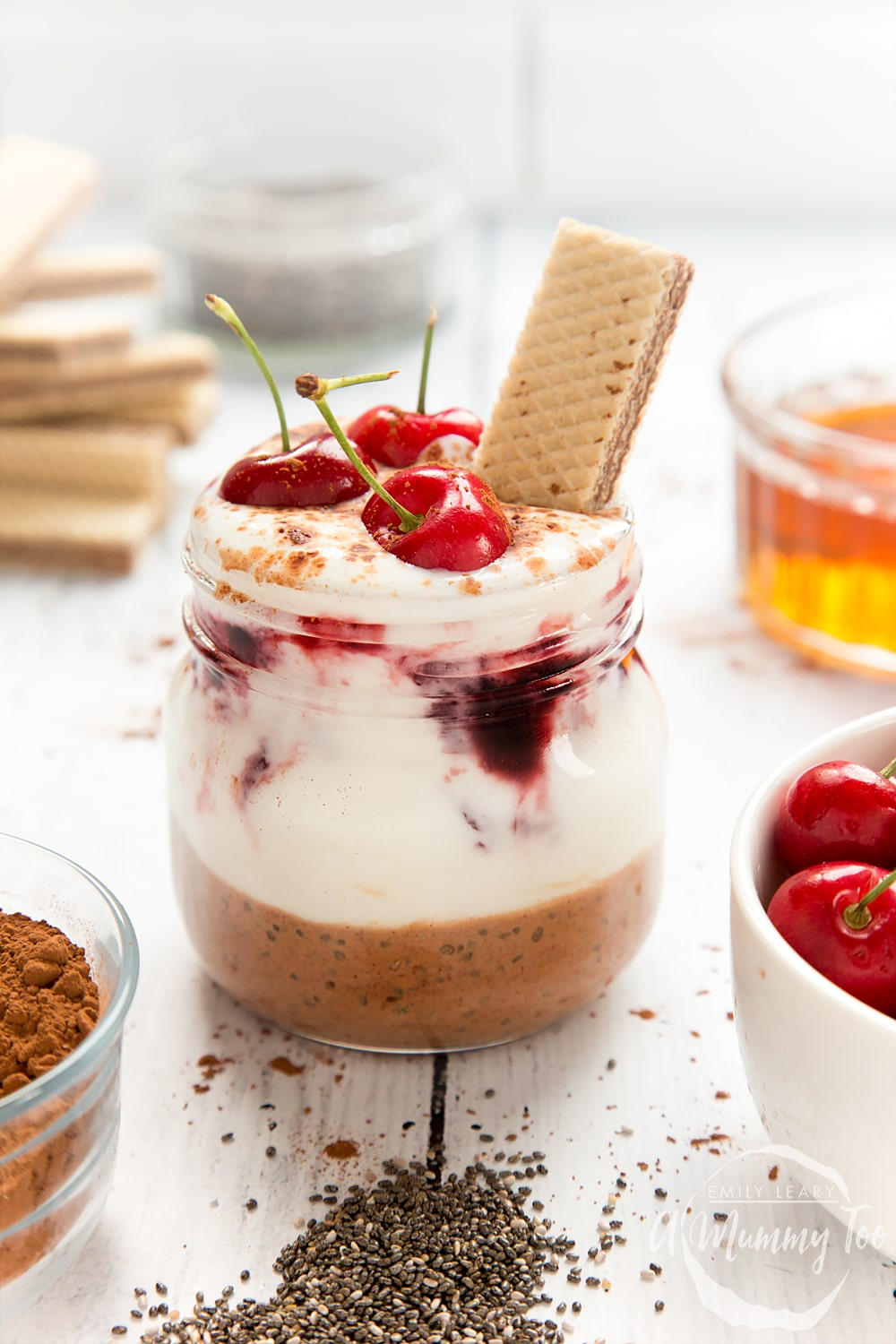 This black forest breakfast jar features layers of yogurt and cherry conserve, topped with cherries and a Loacker Napolitaner wafer
