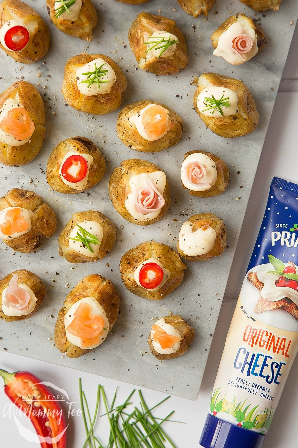 Stuffed mini baked potatoes topped with Primula cheese, peppers, chives, ham and salmon - a delicious festive starter or snack