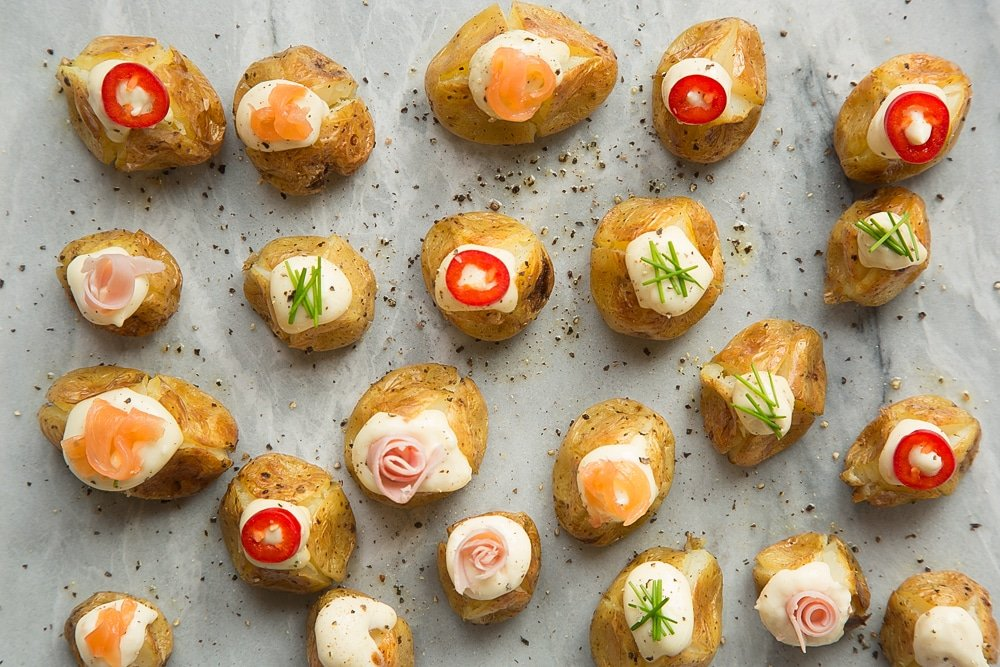 Top the stuffed mini baked potatoes with toppings of your choice - shown here is pepper, chives, salmon and ham
