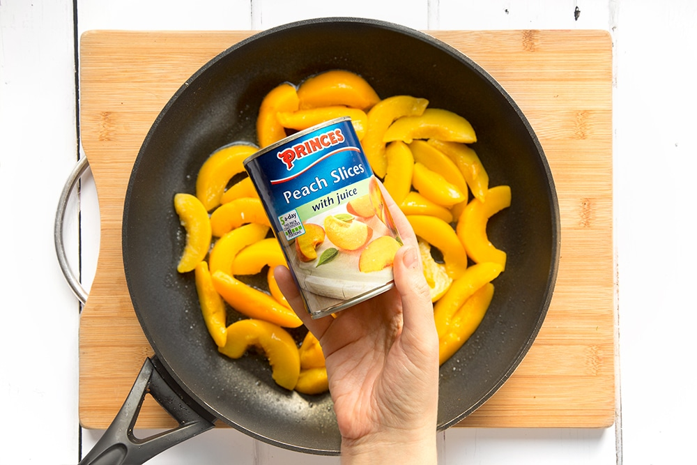 Princes peach slices with juice are added to the frying pan