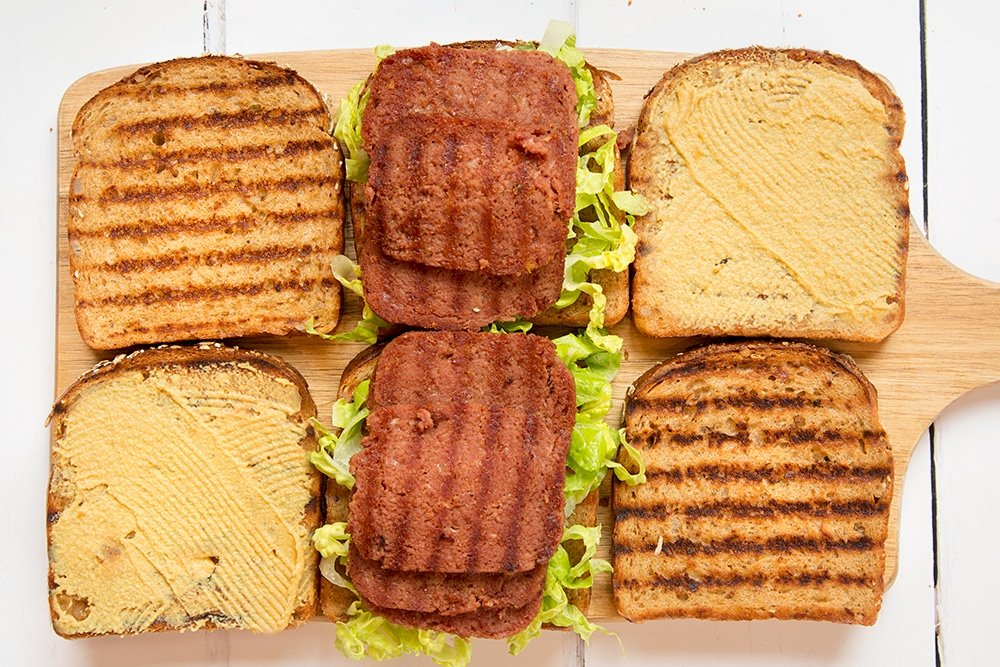Preparing the deli-style corned beef on rye sandwich by adding lettuce and slices of corned beef, as well as mustard