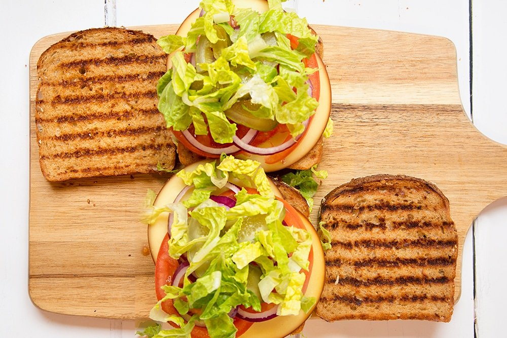 Gherkins and lettuce are added to the final layer of the sandwich