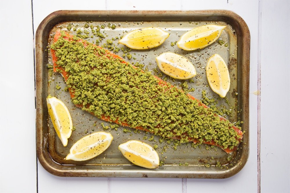 Lemon wedges are added to the Alaska salmon fillet ready to bake