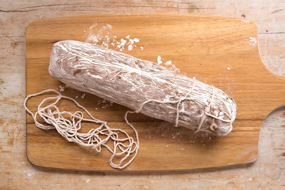 Decorating the Christmas spiced chocolate salami with food-safe string