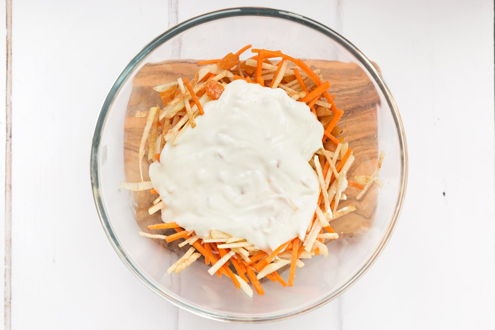 Mixing Onken plain grain yogurt into the sliced fruit and carrot