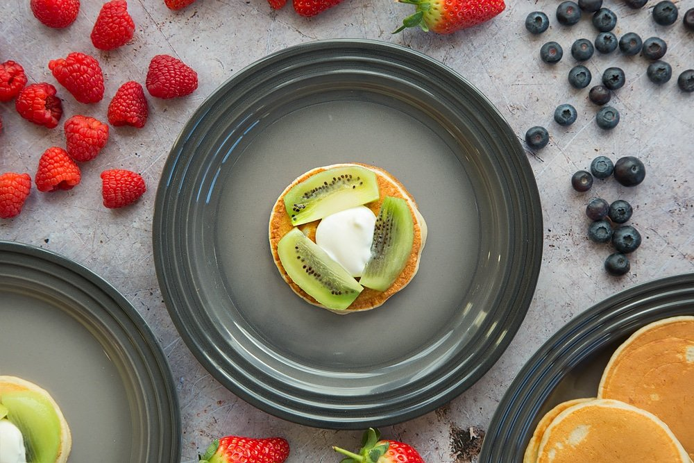 Start building your fruity pancake stack with a pancake topped with kiwi and yogurt