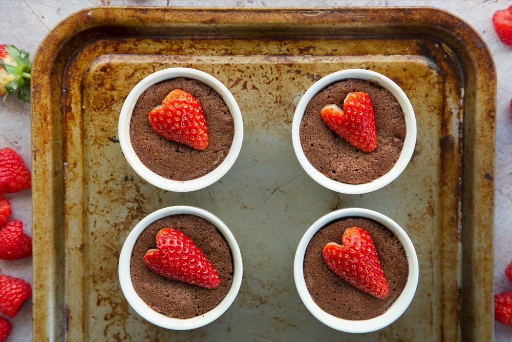 The strawberry hot chocolate puddings are topped with a strawberry each to finish