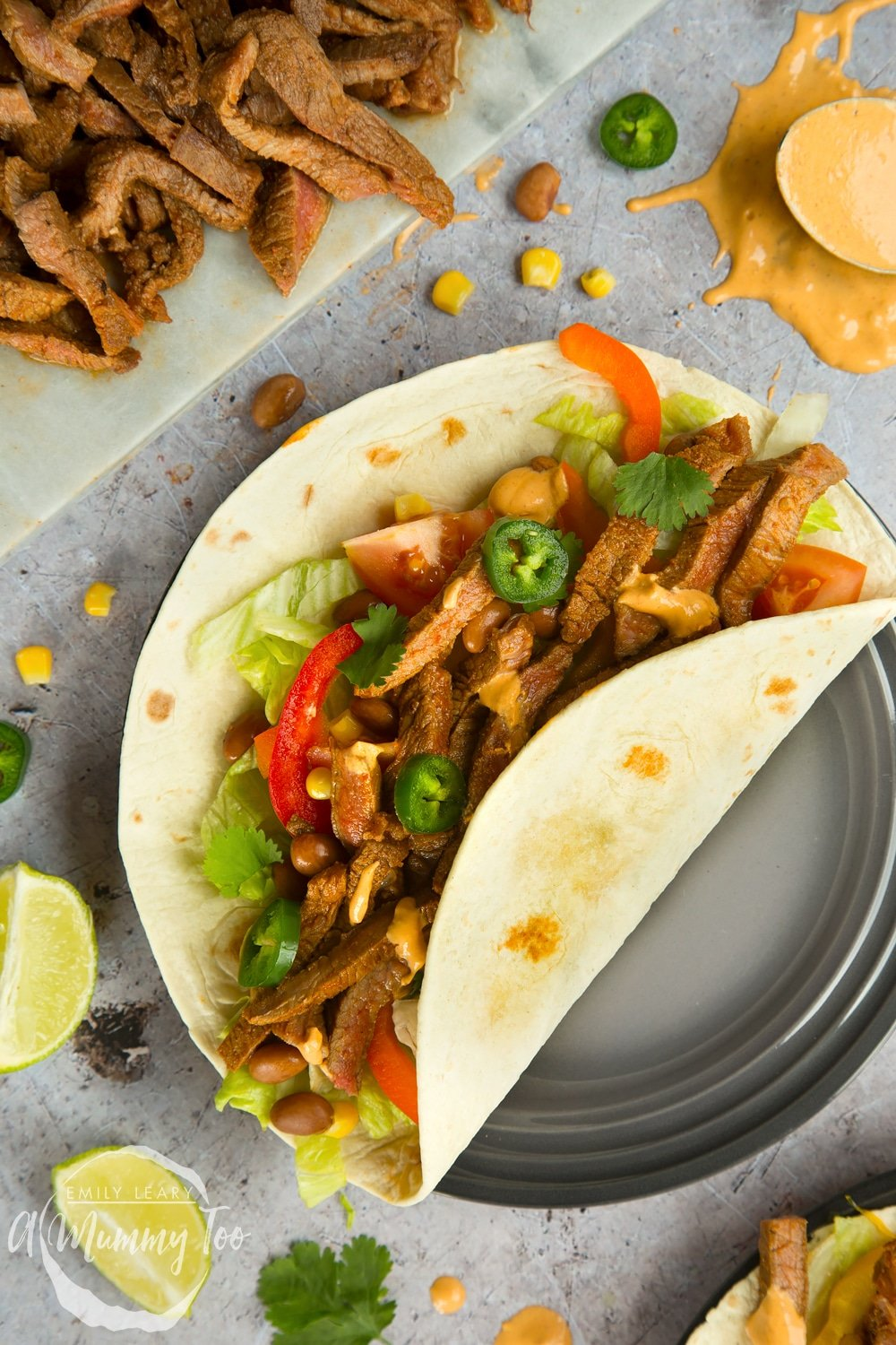 Serve everything to the table, with added accompaniments, for everyone to assemble their own spicy chipotle beef carne asada fajitas!
