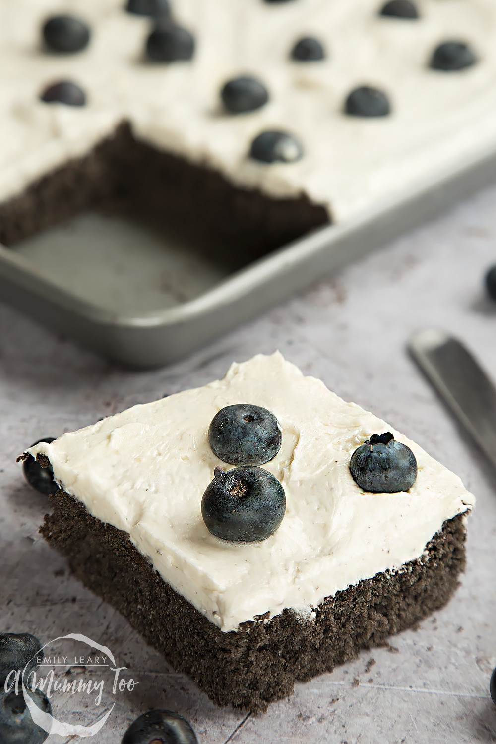 A slice of black velvet sheet cake with classic velvet frosting, topped with blueberries