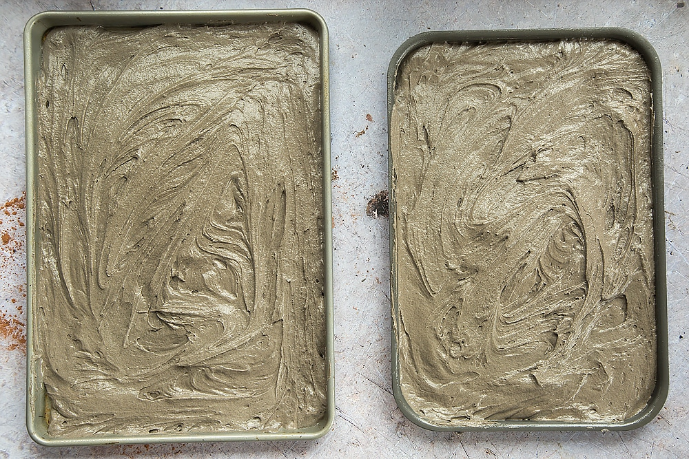 The cake mix is spread around the tins and leveled out, ready for baking