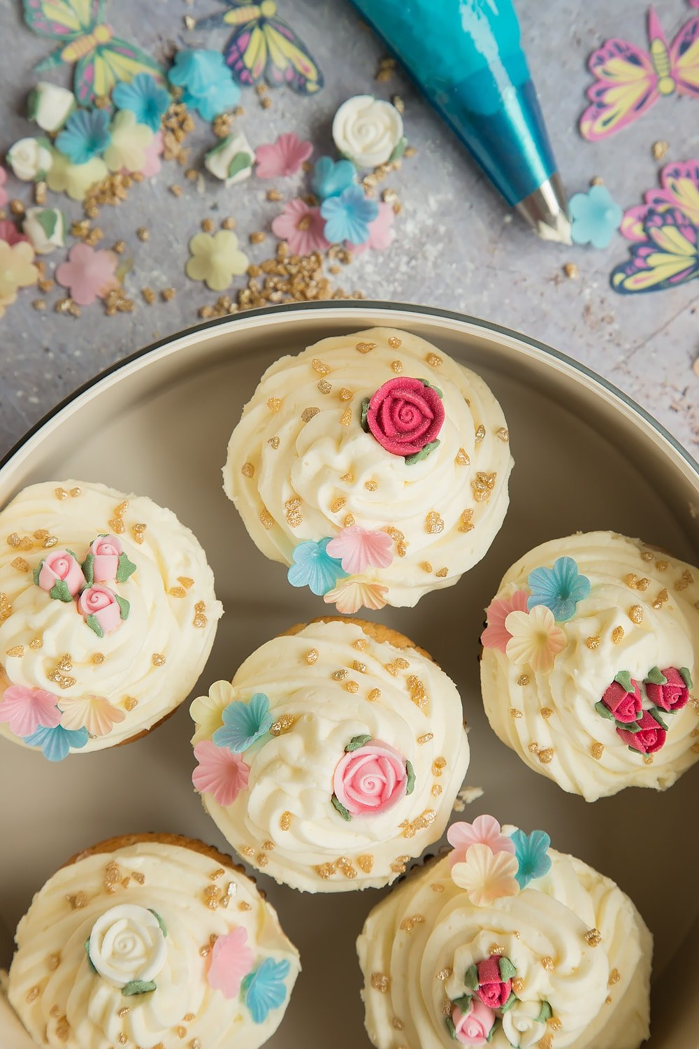 Lemon cupcakes with buttercream frosting, surrounded by decorations