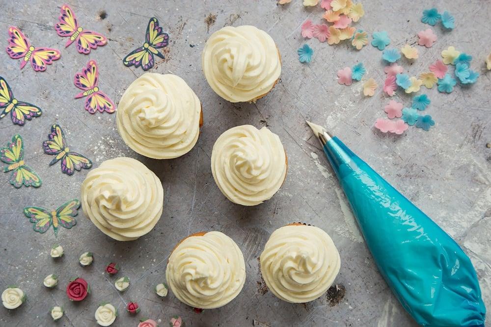 Generous swirls of lemon buttercream icing on top of the lemon cupcakes