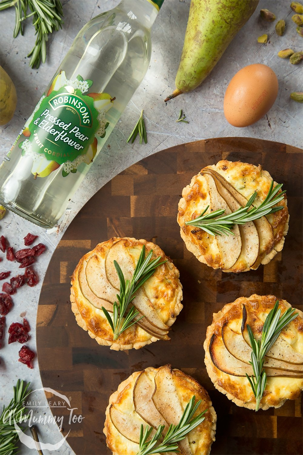 Overhead shot of a set of rosemary goat's cheese tarts with sliced bear with a botte of the Robbinsons pressed pear & elderflower on the side.