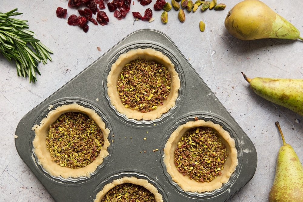 The cranberry and pistachio mix, spooned carefully into the tarts