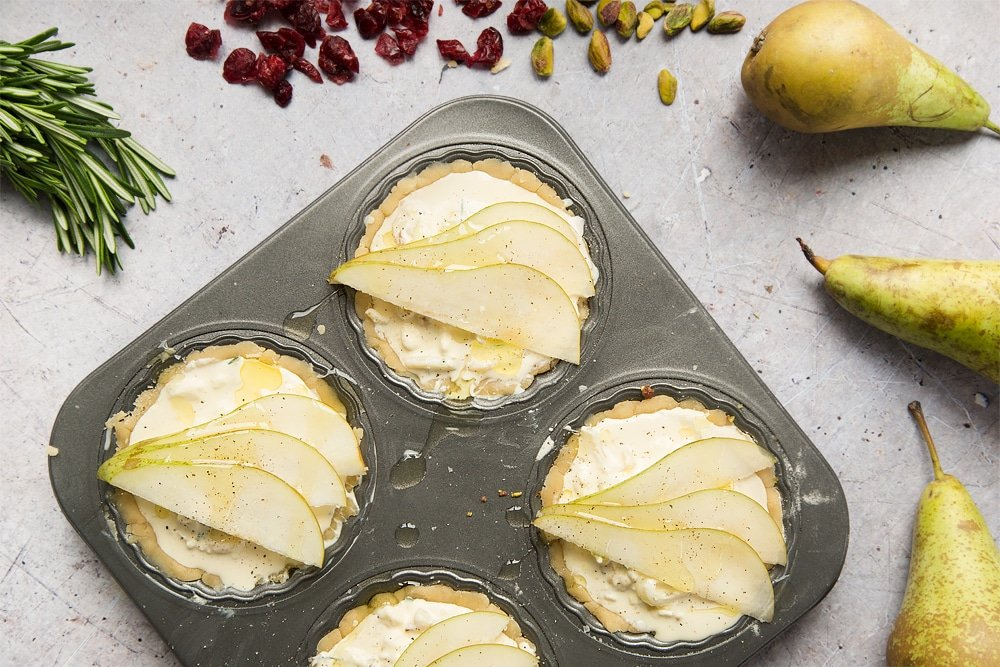 The finished rosemary goat's cheese tarts are topped with sliced pear
