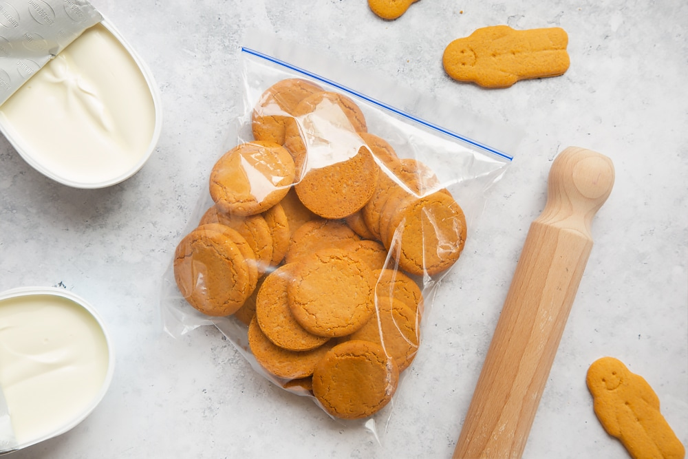 Overhead shot of biscuits inside ziplock bag with a wooden rolling pin on the side