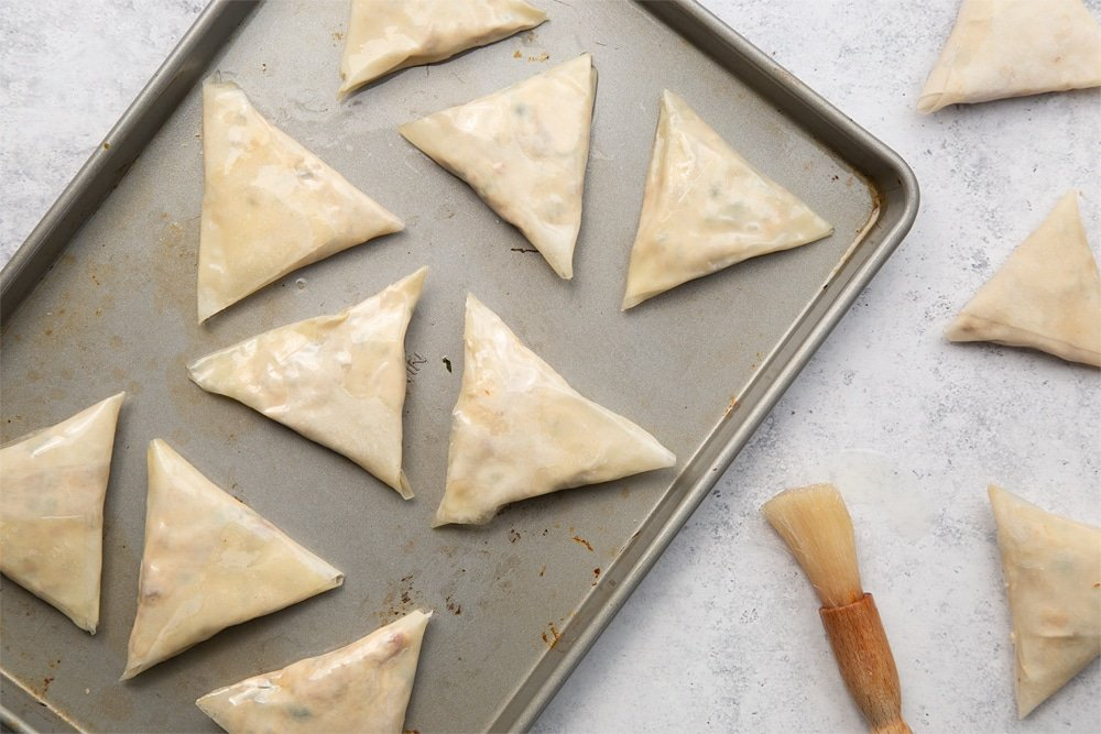 Brush your olive and sun-dried tomato filo parcels with oil and place on a baking tray