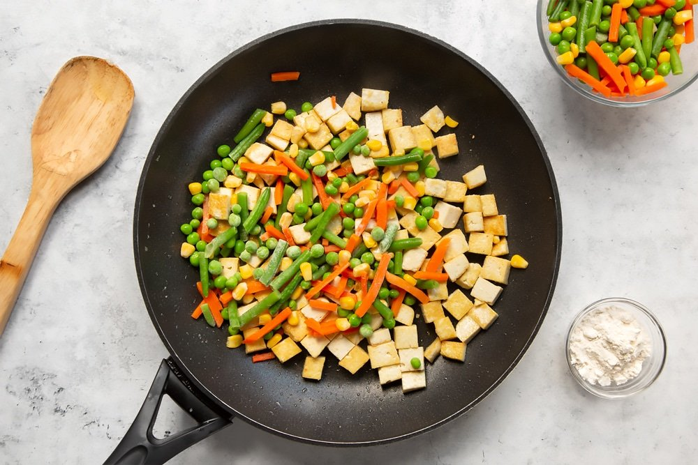 Add the frozen vegetables to the tofu and fry