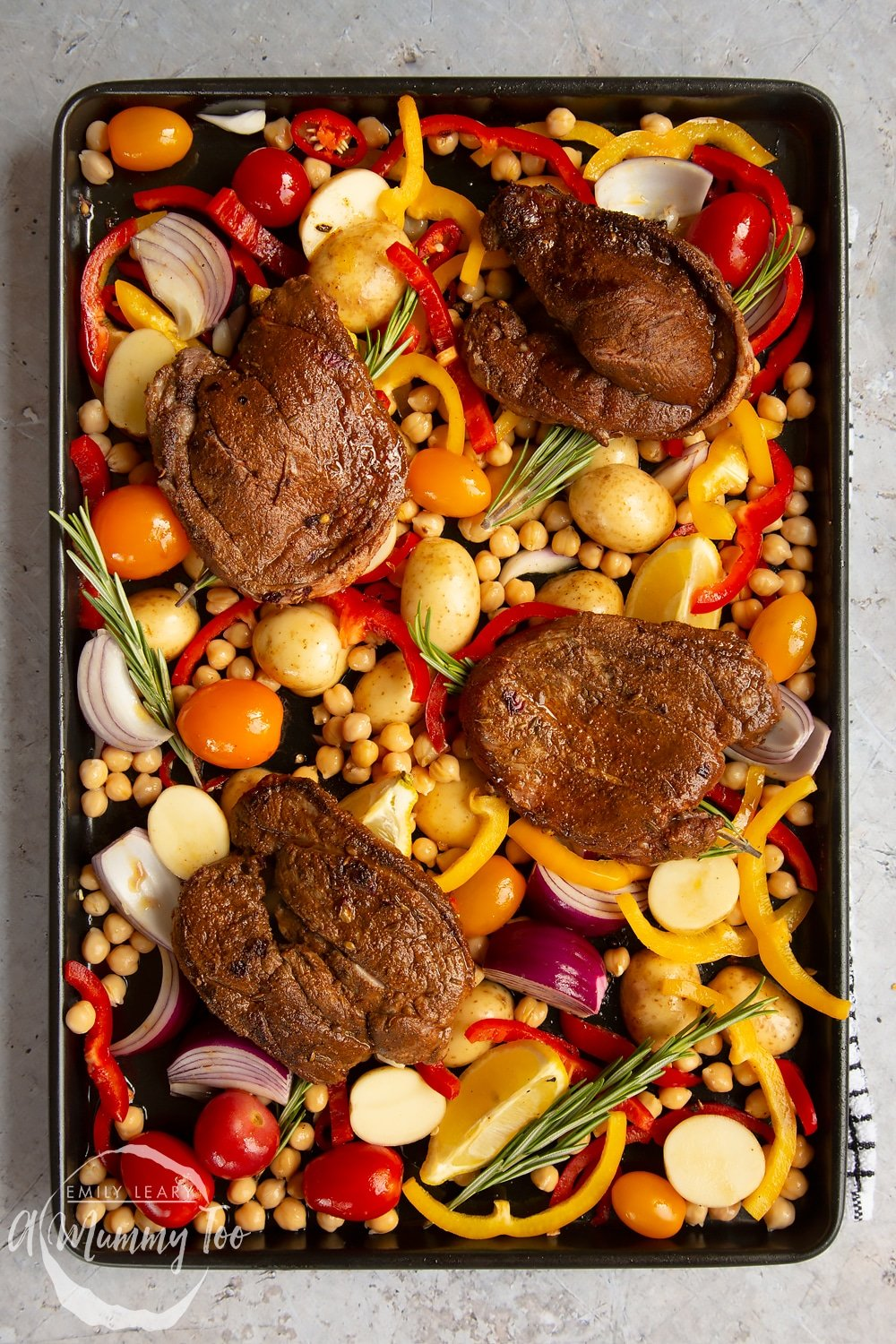 Lamb steaks placed on top of the vegetables and rosemary