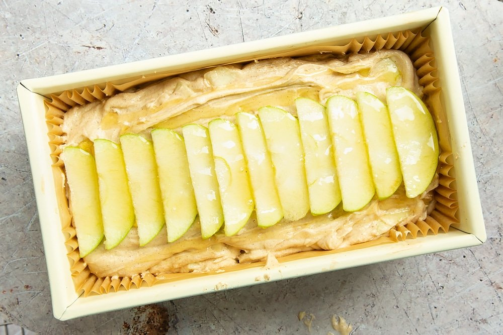 The apple, cinnamon and honey cake in a loaf tin, topped with sliced apples and drizzled with honey