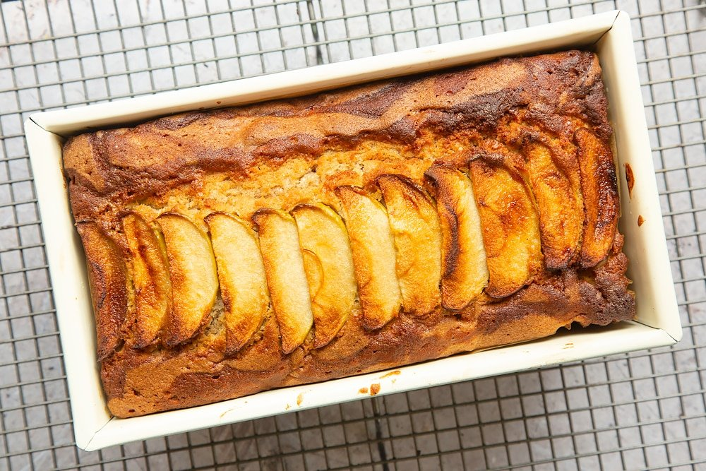 Freshly baked apple, cinnamon and honey cake in a loaf tin cooling on a wire rack