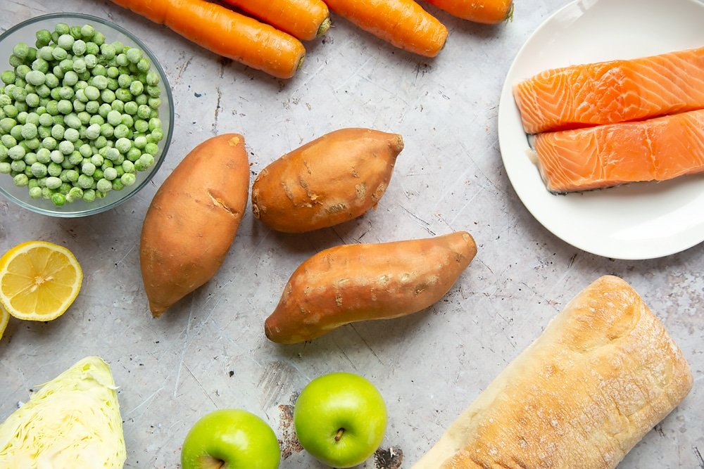 Ingredients to make this healthier fish finger sarnie - sweet potatoes, peas, salmon, bread, apples, carrots and more