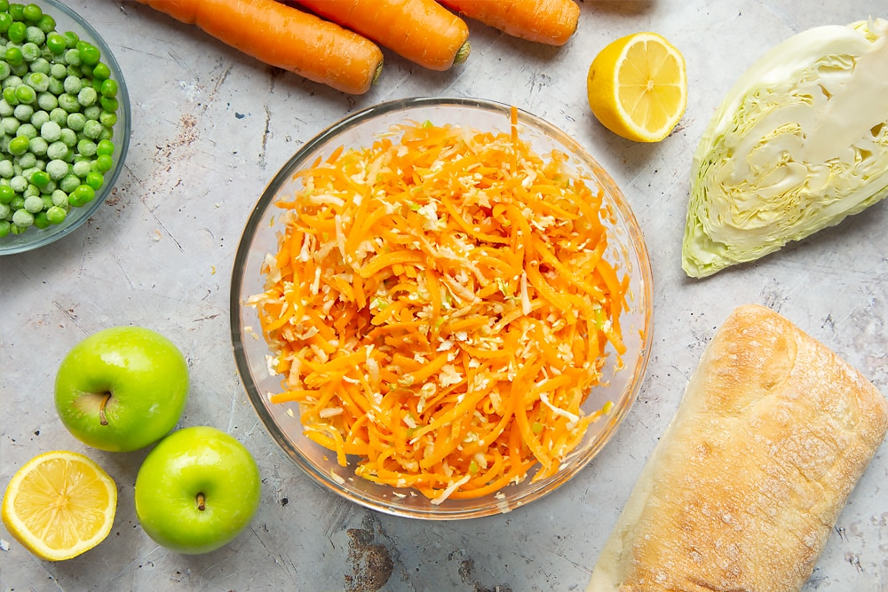 Making coleslaw with cabbage, carrots and apple