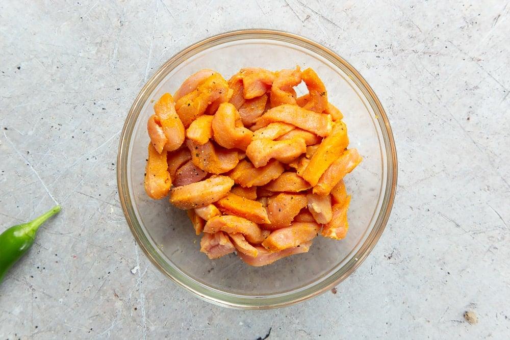 Seasoned strips of pork in a glass bowl