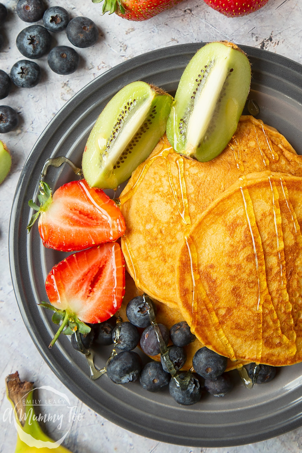 A stack of sweet potato pancakes served with strawberries, kiwi and blueberries