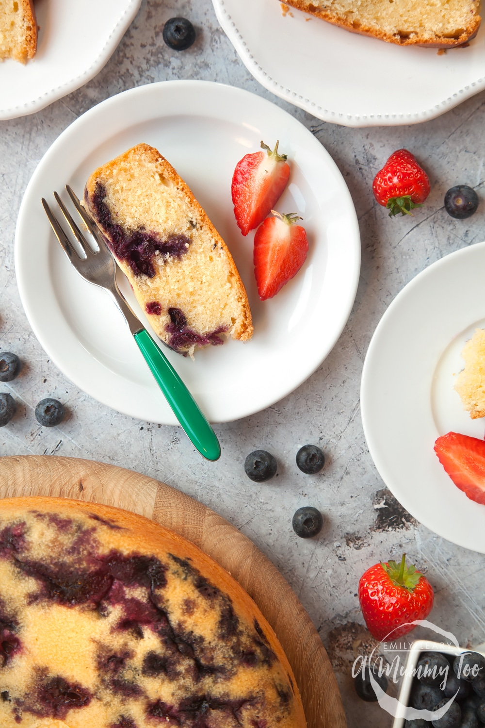 Blueberry cake cut into slices and served with sliced strawberries