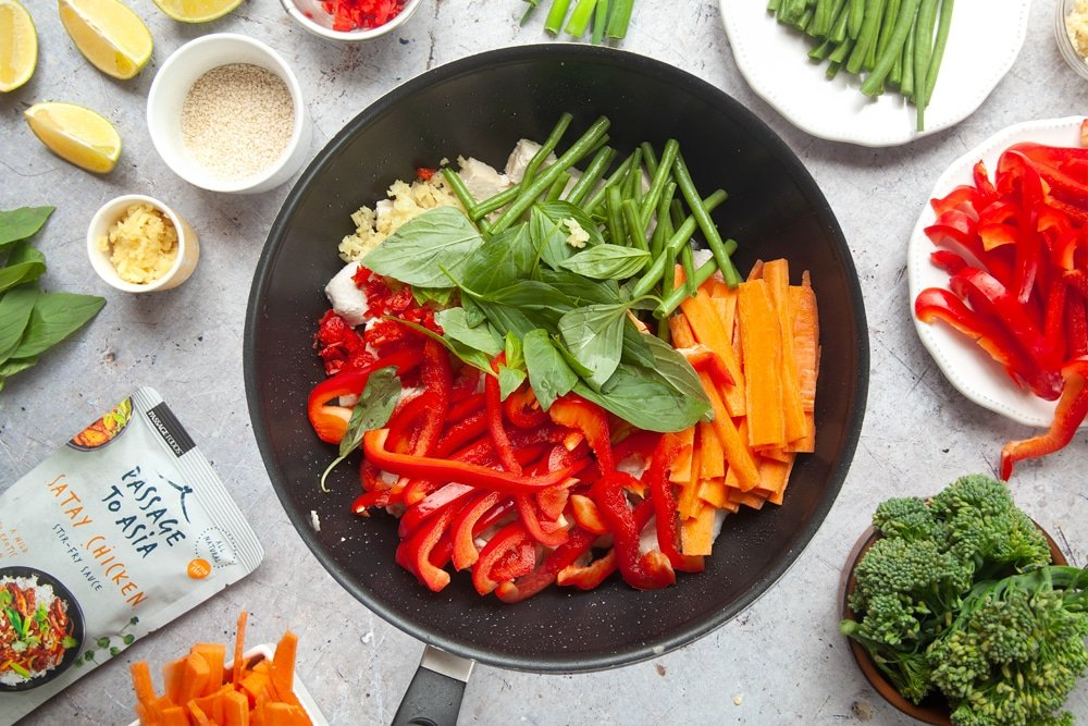 Wok filled with chicken, tofu and colourful vegetables