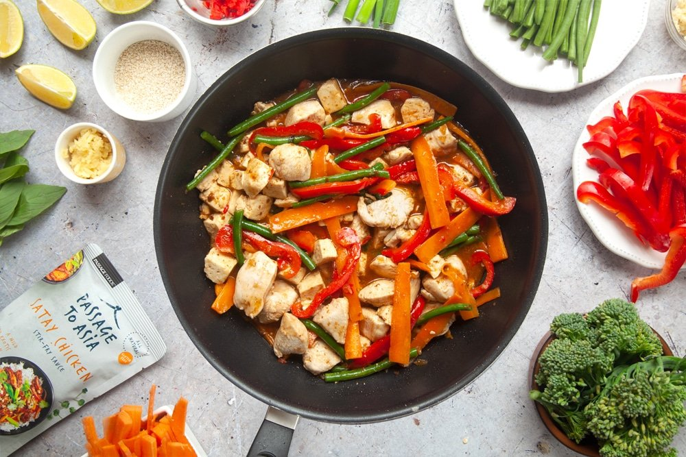 Cooking chicken and tofu satay stir-fry in a wok