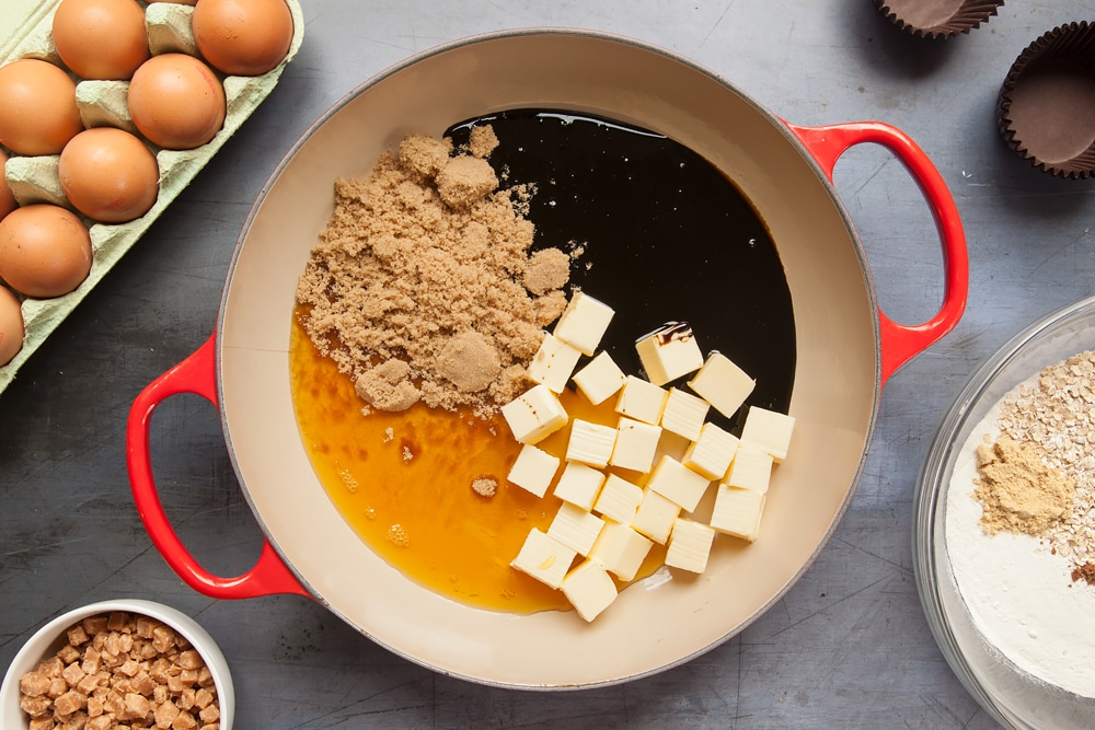 Overhead shot of butter, sugar, eggs, golden syrup, and black treacle in a red pan