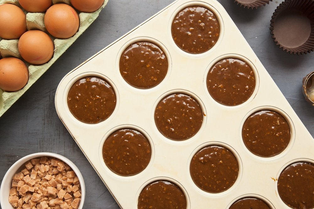 Overhead shot of muffin tray with mixture in a large clear bowl