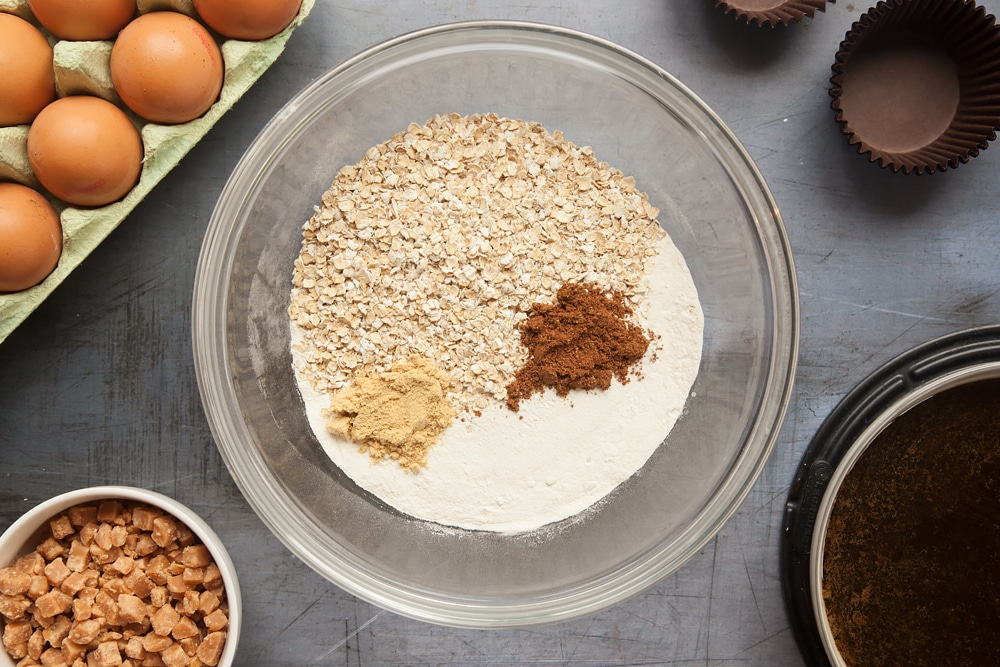 Overhead shot of flour, oats, ginger and mixed spice in a large clear bowl
