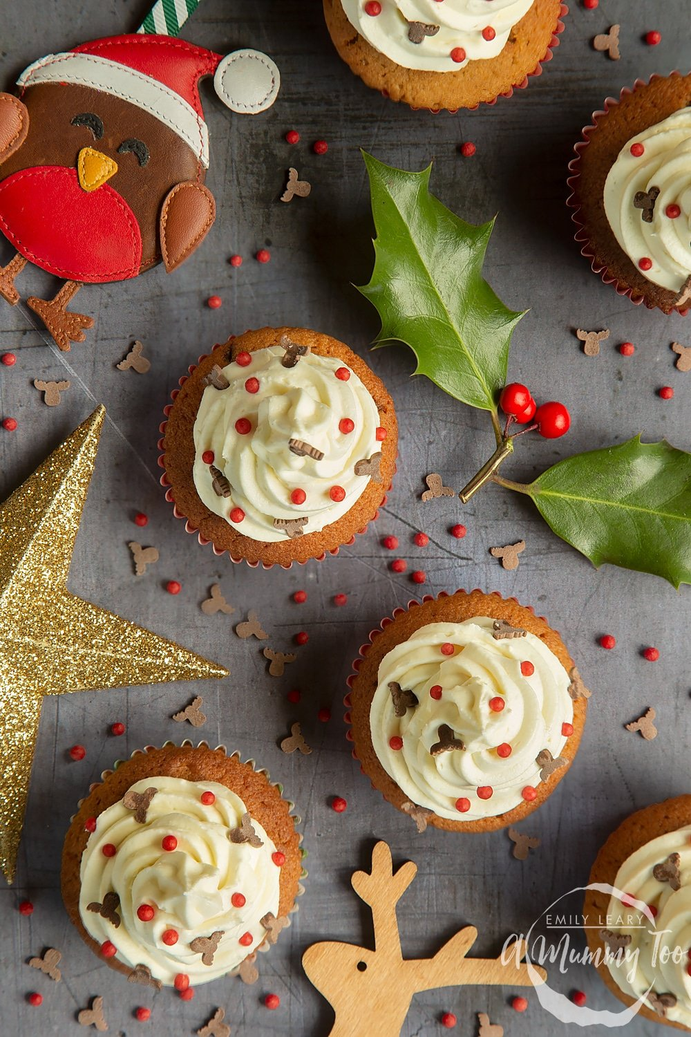 Adding festive sprinkles to the finished spiced Christmas cupcakes with marzipan frosting