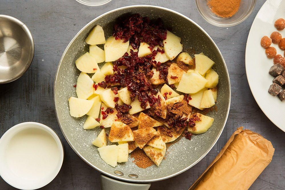 Chopped apple, cranberries and mixed spice in a frying pan